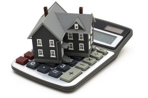 House sitting on calculator isolated on white